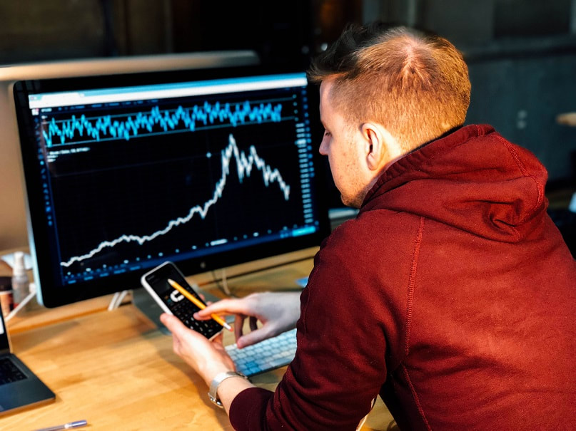 Investor sitting in front of a PC showing a stock chart
